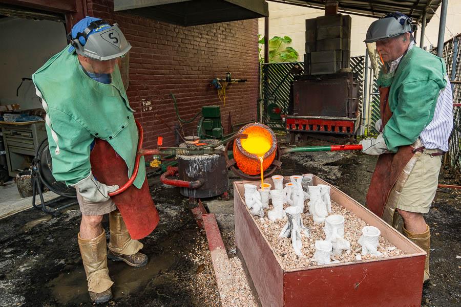 Steven and Stewart Wegner pouring molten bronze into molds.